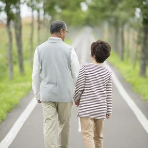 手をつなぎ一本道を歩くシニア夫婦の後姿の写真素材 [FYI04554227]