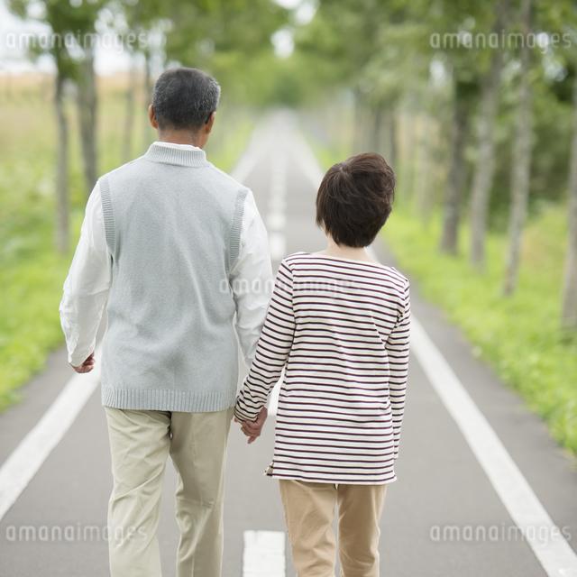 手をつなぎ一本道を歩くシニア夫婦の後姿の写真素材 [FYI04554230]