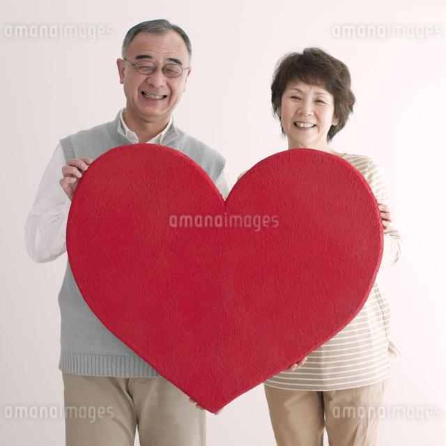 ハートを持ち微笑むシニア夫婦の写真素材 [FYI04554236]