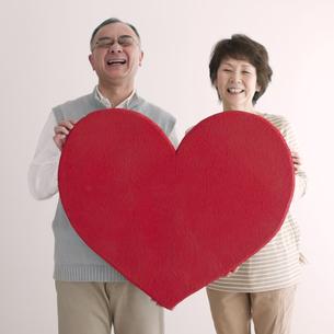 ハートを持ち微笑むシニア夫婦の写真素材 [FYI04554237]