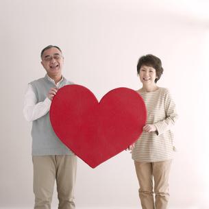 ハートを持ち微笑むシニア夫婦の写真素材 [FYI04554239]