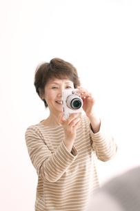 カメラを持ち微笑むシニア女性の写真素材 [FYI04554247]
