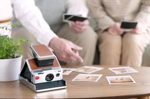 ポラロイドの写真を見るシニア夫婦の手元の写真素材 [FYI04554260]