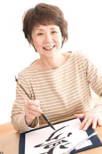書道をするシニア女性の写真素材 [FYI04554279]