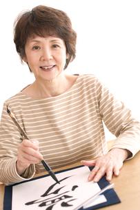 書道をするシニア女性の写真素材 [FYI04554280]