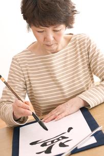 書道をするシニア女性の写真素材 [FYI04554285]