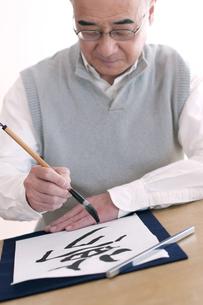 書道をするシニア男性の写真素材 [FYI04554338]