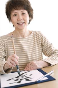 書道をするシニア女性の写真素材 [FYI04554340]
