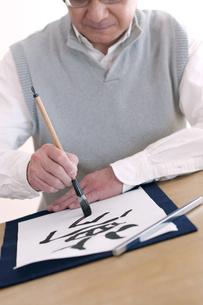書道をするシニア男性の手元の写真素材 [FYI04554341]