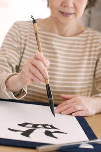 書道をするシニア女性の手元の写真素材 [FYI04554369]