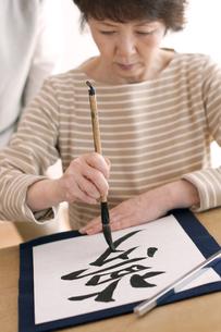 書道をするシニア女性の写真素材 [FYI04554376]