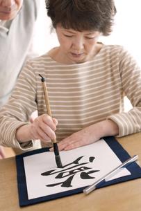 書道をするシニア女性の写真素材 [FYI04554379]