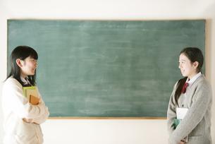 黒板の前で向き合う中学生の写真素材 [FYI04554462]