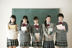 黒板の前で微笑む中学生の写真素材 [FYI04554480]