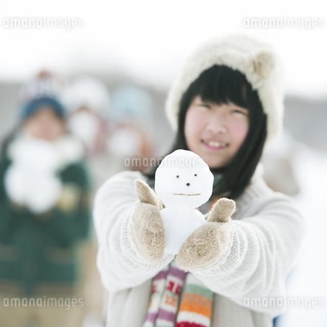 雪だるまを持ち微笑む中学生の写真素材 [FYI04554556]