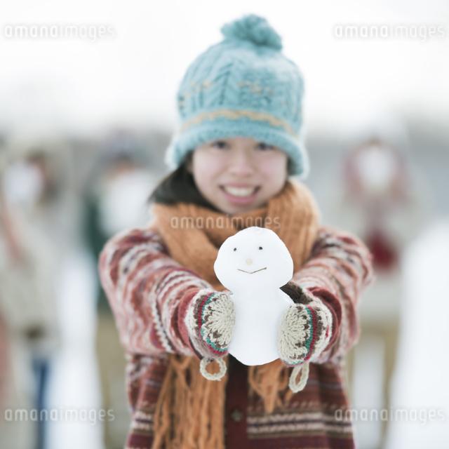 雪だるまを持ち微笑む中学生の写真素材 [FYI04554558]