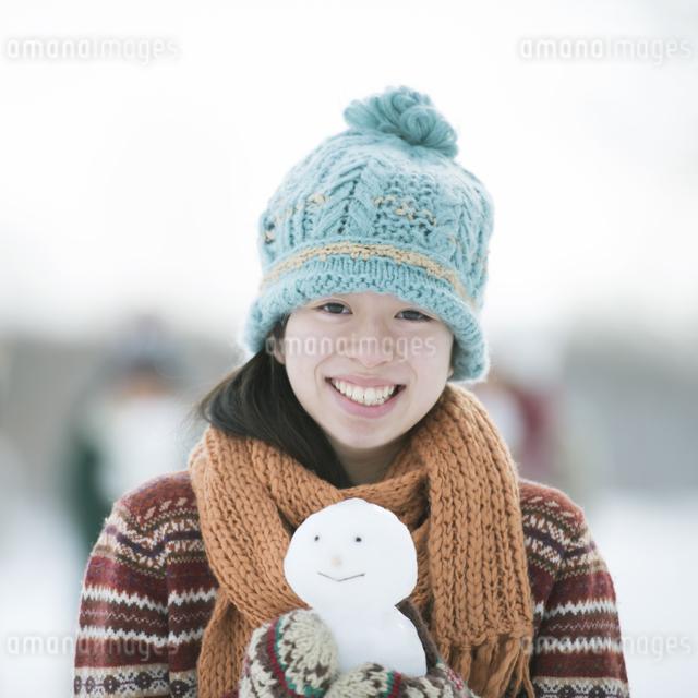 雪だるまを持ち微笑む中学生の写真素材 [FYI04554565]