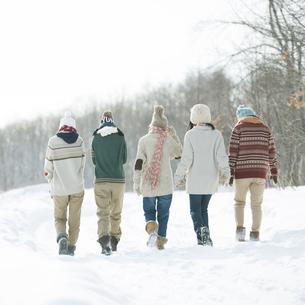 雪道を歩く中学生の後姿の写真素材 [FYI04554627]