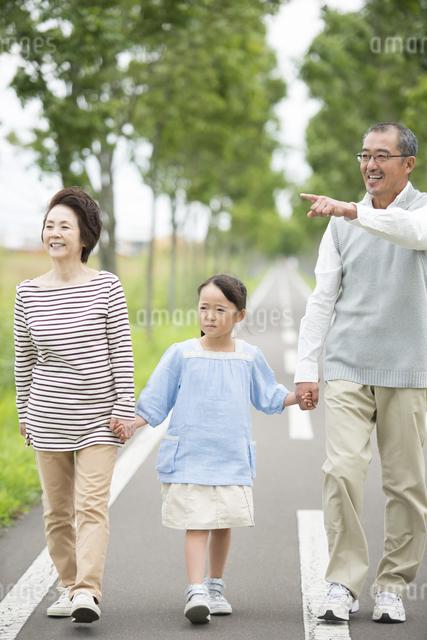一本道で手をつなぐ祖父母と孫の写真素材 [FYI04554646]