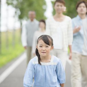 一本道で微笑む女の子と見守る家族の写真素材 [FYI04554664]