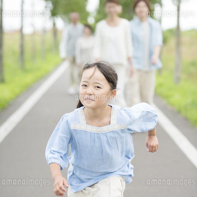 一本道を走る女の子と見守る家族の写真素材 [FYI04554667]