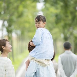 肩車をする親子と祖父母の後姿の写真素材 [FYI04554694]