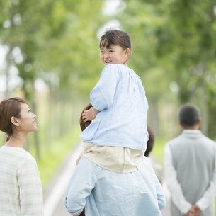 肩車をする親子と祖父母の後姿の写真素材 [FYI04554696]