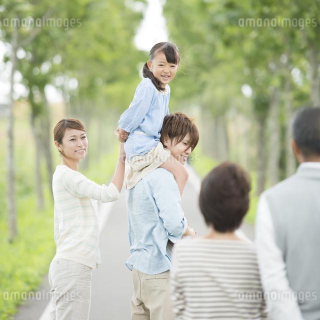 一本道で肩車をする親子と祖父母の写真素材 [FYI04554711]