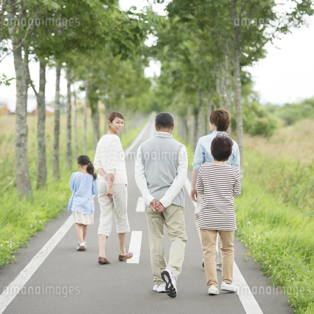 一本道を歩く3世代家族の後姿の写真素材 [FYI04554715]