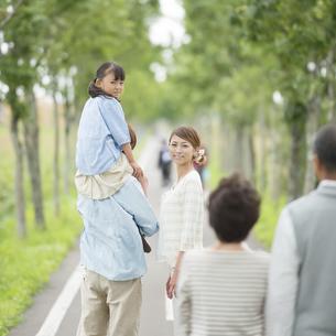 一本道で肩車をする親子と祖父母の写真素材 [FYI04554716]