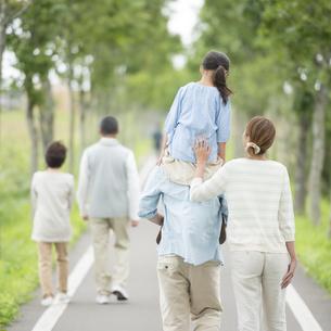 一本道で肩車をする親子と祖父母の後姿の写真素材 [FYI04554718]