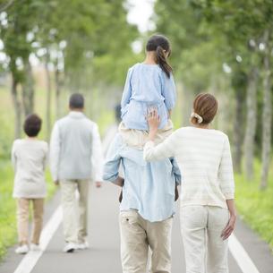 一本道で肩車をする親子と祖父母の後姿の写真素材 [FYI04554719]