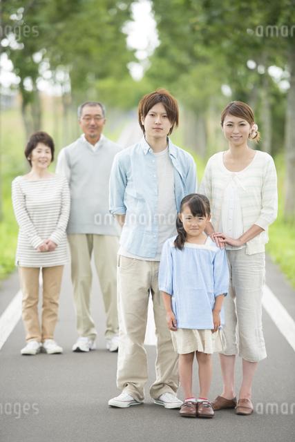 一本道で微笑む3世代家族の写真素材 [FYI04554727]