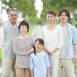 一本道で微笑む3世代家族の写真素材 [FYI04554736]