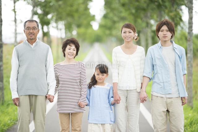 一本道で手をつなぐ3世代家族の写真素材 [FYI04554741]