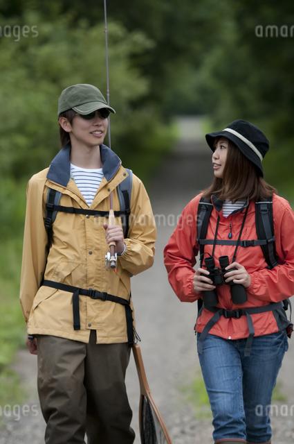 一本道を歩くカップルの写真素材 [FYI04554766]