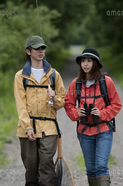 一本道を歩くカップルの写真素材 [FYI04554767]