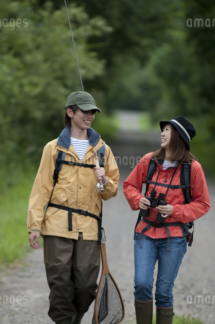 一本道を歩くカップルの写真素材 [FYI04554772]