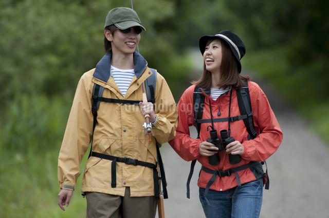 一本道を歩くカップルの写真素材 [FYI04554773]