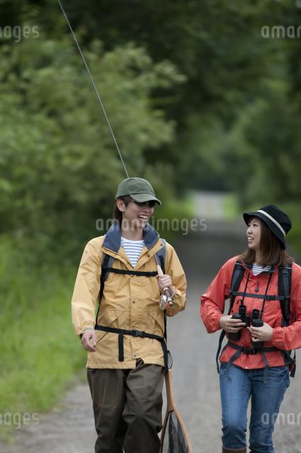 一本道を歩くカップルの写真素材 [FYI04554774]