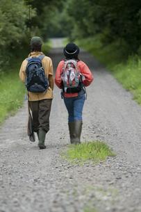 一本道を歩くカップルの後姿の写真素材 [FYI04554777]
