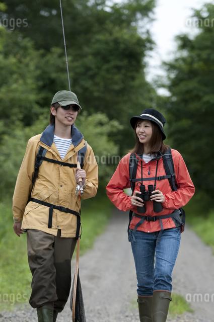 一本道を歩くカップルの写真素材 [FYI04554778]