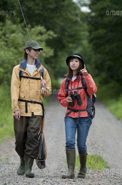 一本道を歩くカップルの写真素材 [FYI04554779]