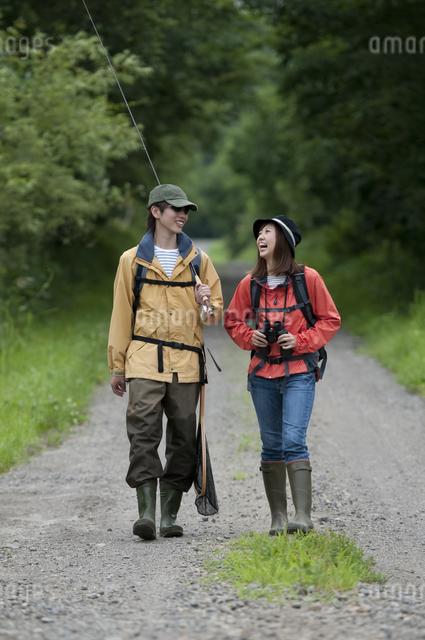 一本道を歩くカップルの写真素材 [FYI04554780]