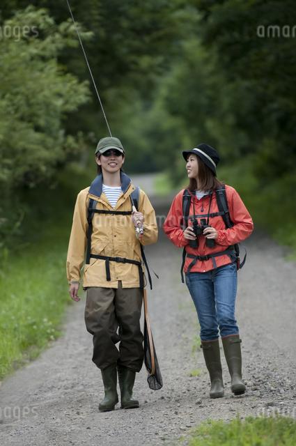 一本道を歩くカップルの写真素材 [FYI04554781]