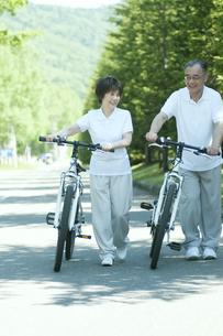 自転車を押すシニア夫婦の写真素材 [FYI04554887]