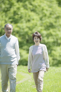 草原を歩くシニア夫婦の写真素材 [FYI04554922]