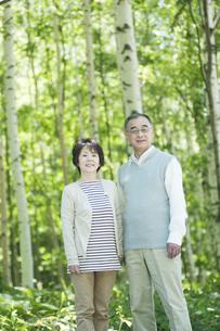 森林の中で微笑むシニア夫婦の写真素材 [FYI04554951]