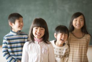 黒板の前で微笑む小学生の写真素材 [FYI04555021]