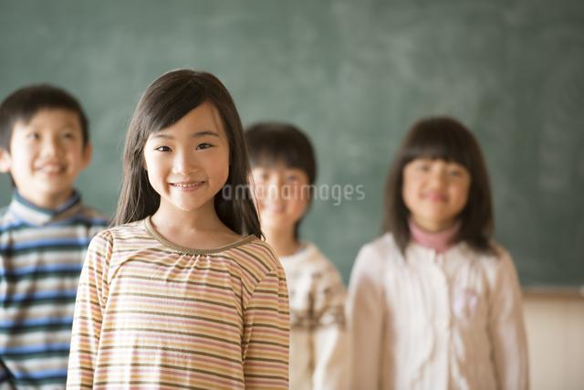 黒板の前で微笑む小学生の写真素材 [FYI04555024]